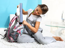 Girl put the book into a backpack Stock Images
