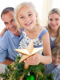 The girl put the Christmas star on top the tree royalty free stock image