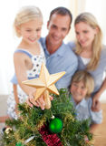 The girl put the Christmas star on top of the tree. Father lifting his daughter to put the Christmas star on top of the tree at home royalty free stock photography