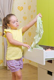 Girl put a clothes to case box in a  home Royalty Free Stock Photo