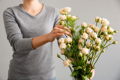 Girl put flowers in vase over gray background. Royalty Free Stock Image