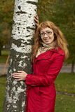 A girl put her arms around the trunk of a birch t tree with golden hair wearing glasses in a bright scarf cool summer slight smile Stock Photo