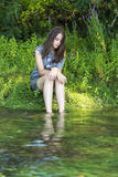 Girl put her feet in the river. Photographed on the beach of the river Drina stock image