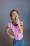 Girl put her hand over mouth yawns Royalty Free Stock Photo