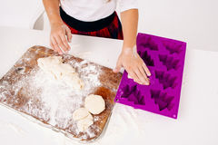 Girl put raw dough into form for cakes, top view Royalty Free Stock Photography