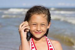 Girl put to the ear sea shell. Beautiful little girl put to the ear sea shell Royalty Free Stock Image