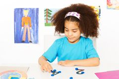 Girl puts blue coins learning to count. African girl puts blue coins on numbers learning to count during developmental game at the desk while sitting in playroom stock image