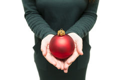 Girl puts christmas ball in hand Royalty Free Stock Photography