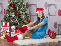 Girl puts Christmas socks, sitting by the Christmas tree Stock Images