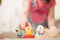 The girl puts the decorated egg on homemade stands rabbits. Classes with children in preparation for Easter. Children`s creativity. Copy space text Royalty Free Stock Photos