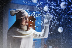 Girl puts decorations on the Christmas tree in a snow day Royalty Free Stock Image