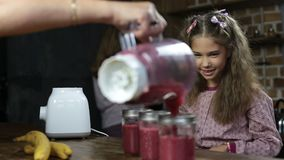 Girl puts drinking straws into jars with smoothie stock footage