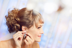 Girl puts on an earring Stock Images