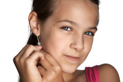 Girl puts earrings Stock Images