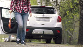 Girl puts emergency stop sign and sits to the car stock video footage