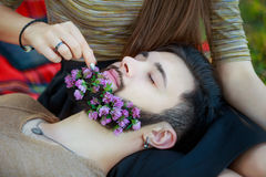 Girl puts a flower in his beard Man Royalty Free Stock Photography