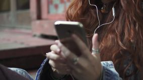 Girl puts on headphones and turns the music on your mobile phone. 20s. Girl listening to music on headphones sitting on wooden steps and moving to the beat of stock video footage