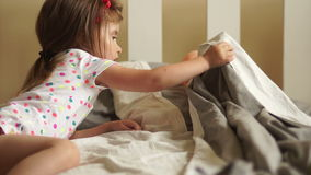 A girl puts her doll to bed. She carefully covers it with a blanket. Children`s games. Mother`s daughters stock footage