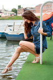Girl puts her foot into the water holding on to the railing Royalty Free Stock Photography