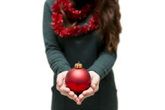 Girl puts her hands together in the shape of a heart and Christm. As tree bauble lies on them Stock Photo