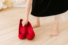 The girl puts on her mother`s shoes. Mother`s shoes in children`s hands. Why kids love to try on clothes of parents. The girl puts on her mother`s shoes. Mother` stock photography