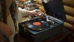 Girl puts music record on an old retro gramophone stock video