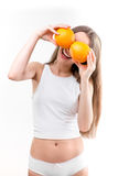 Girl puts oranges on her eyes stock photos