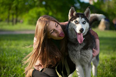 The girl puts out one's tongue the same as her dog Royalty Free Stock Photography