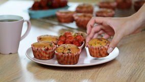 Girl puts a plate of muffins stock footage