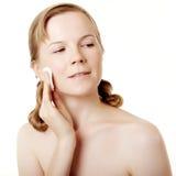 Girl puts on skin cream Royalty Free Stock Image