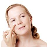 Girl puts on skin cream Royalty Free Stock Photo
