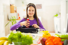 Girl puts a snack in a bag for school Royalty Free Stock Photos