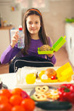Girl puts a snack in a bag for school Stock Images