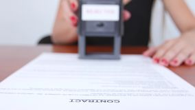 Girl puts the stamp of the firm on the contract. Close up stock video