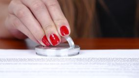 Girl puts a stamp by little pocket signet. Close up stock video footage