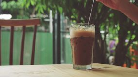 Girl puts straw in glass of iced coffee. stock footage