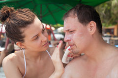 Girl puts sun-protection cream on a man's Stock Image