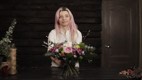 A girl puts on a table a decorated bouquet of flowers. Surprised and laughs. Bouquet in the foreground. The dark. Interior. Slow motion stock footage