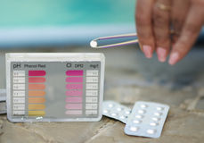 Girl puts a tablet tester for testing Ph and chlorine. Stock Photo