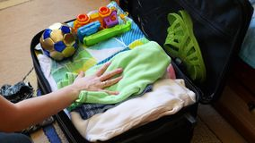 Girl puts things in the suitcase for travel in closeup. Girl puts things in the suitcase closeup stock footage