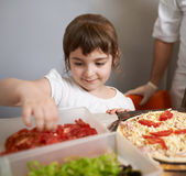 Girl puts tomatoes on  pizza Royalty Free Stock Images