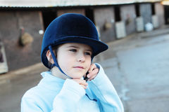 Girl puttin on riding helmet Stock Images