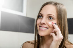 Girl putting anti-aging cream Royalty Free Stock Photos