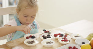 Girl putting berries on muffins  table Stock Photo