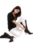 Girl putting on boots. A young pretty woman sitting on the floor in white pants and a black Royalty Free Stock Photos
