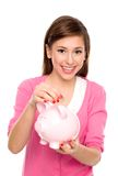 Girl putting coin in piggy bank Stock Photos