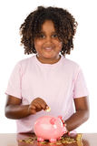 Girl putting a coin in a piggy bank Royalty Free Stock Image
