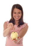 Girl putting coin in piggy bank royalty free stock photos