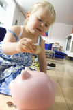 Girl (2-4) putting coin in piggy bank, low angle view Stock Photo