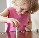Girl putting coins Stock Images
